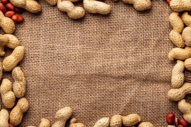 Bovenaanzicht kopieer ruimte pinda's in de schaal en met gepelde pinda's op jute achtergrond