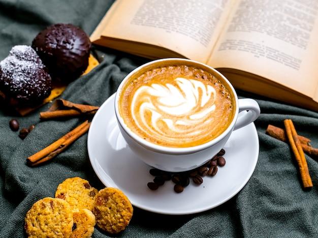 Bovenaanzicht kopje cappuccino met chocolade koekjes en rozijnen koekjes en met een boek op tafel