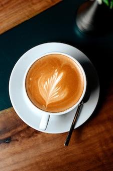 Bovenaanzicht kopje cappuccino met een bloemblad patroon