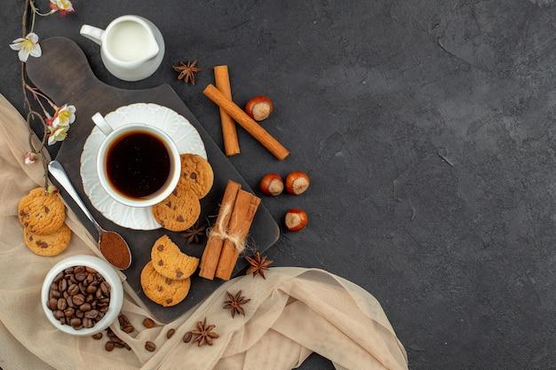 Bovenaanzicht kopje koffie anijs koekjes lepel op houten bord koffiebonen in kom op donkere ondergrond