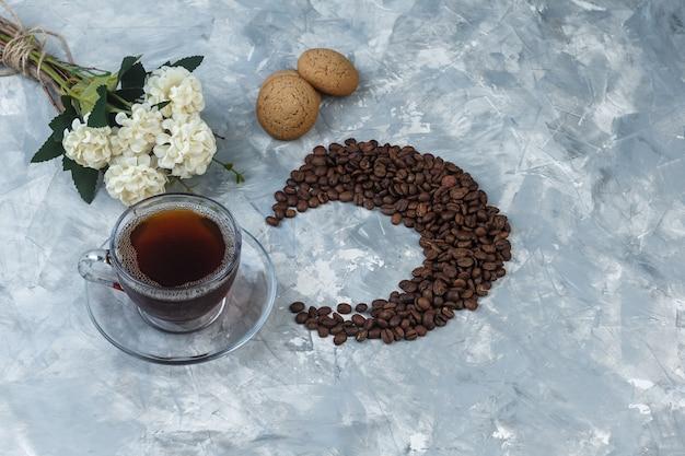 Bovenaanzicht kopje koffie, koekjes met koffiebonen, bloemen op lichtblauwe marmeren achtergrond. horizontaal