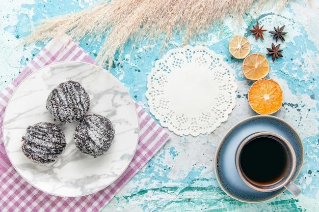 Bovenaanzicht kopje koffie met chocolade glazuur taarten op lichtblauwe achtergrond cake bakken zoete suikertaart koekje