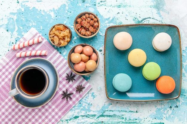Bovenaanzicht kopje koffie met franse macarons rozijnen en confitures op lichtblauwe ondergrond cake bakken zoete suikertaart biscuit