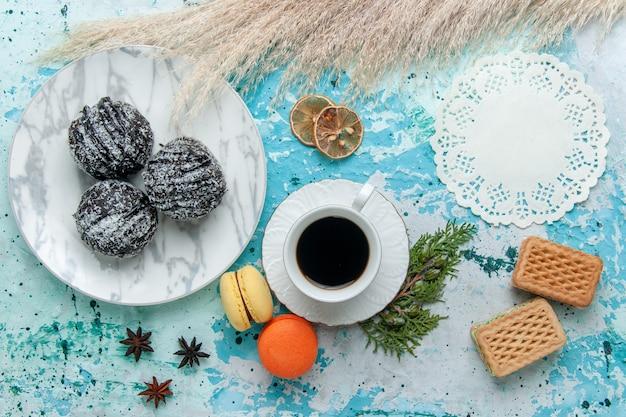 Bovenaanzicht kopje koffie met franse macarons wafels en chocoladetaart op blauw bureau cake bakken koekje zoete chocolade suikerkleur