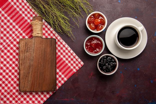 Bovenaanzicht kopje koffie met fruitjams op de donkere achtergrond fruit jam koffie zoet