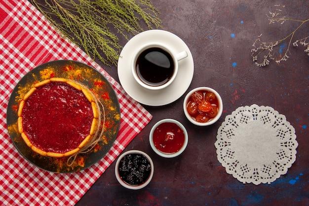 Bovenaanzicht kopje koffie met heerlijke dessertcake en fruitjams op donkere achtergrond zoete vruchten cookie koekje zoet
