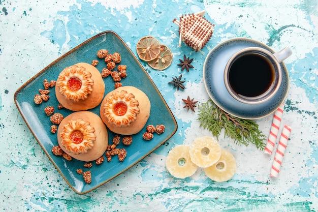 Bovenaanzicht kopje koffie met koekjes op de lichtblauwe kleur van het koekjeskoekje van het bureau