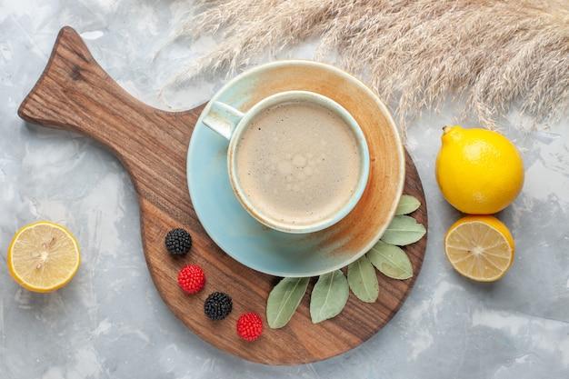 Bovenaanzicht kopje koffie met melk binnen kopje met citroenen op wit bureau drinken koffie melk bureau espresso americano