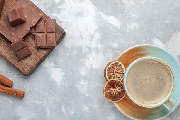 Bovenaanzicht kopje koffie met melk in beker met chocoladerepen en kaneel op wit bureau drinken koffie melk bureau espresso americano