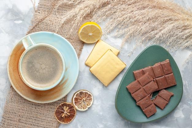 Bovenaanzicht kopje koffie met melk in beker samen met chocolade op licht bureau drinken koffie melk bureau espresso americano