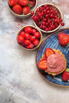Bovenaanzicht kopje koffie met romige cake en fruit op de lichte tafel zoete koektaart
