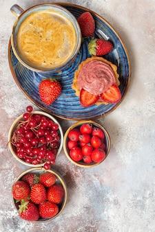 Bovenaanzicht kopje koffie met romige cake en fruit op lichte vloer zoete koektaart