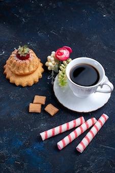 Bovenaanzicht kopje koffie met roze stok snoepjes en cake op blauw