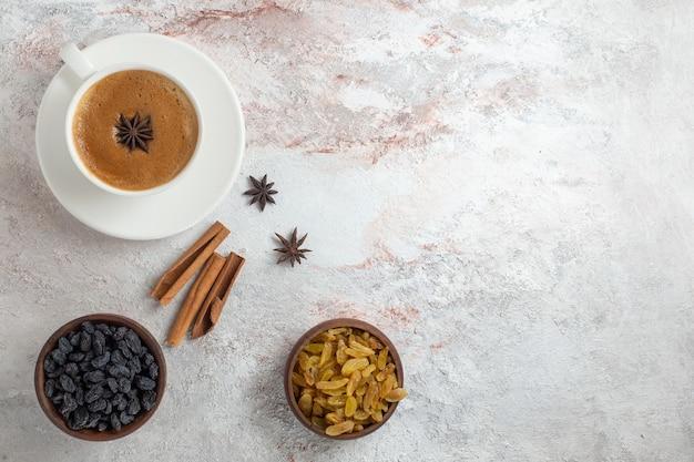 Bovenaanzicht kopje koffie met rozijnen op witte ondergrond