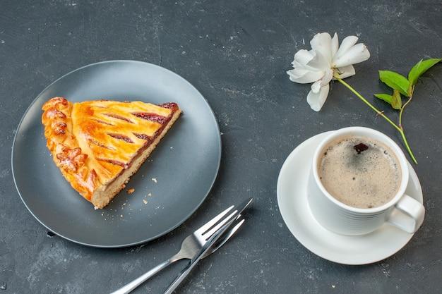 Bovenaanzicht kopje koffie met taartschijfje en witte bloem op donkere tafel