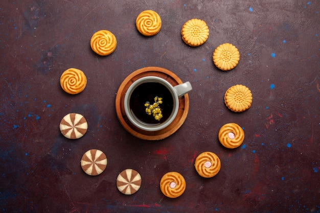 Bovenaanzicht kopje koffie met verschillende koekjes op donkere achtergrond cookie koekje suiker zoete taartcake