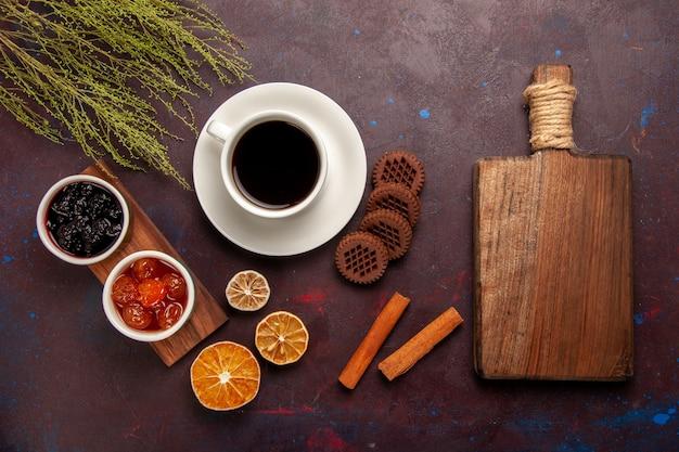Bovenaanzicht kopje koffie met verschillende soorten jam en chocolade koekjes op de donkere achtergrond fruit jam marmelade zoet