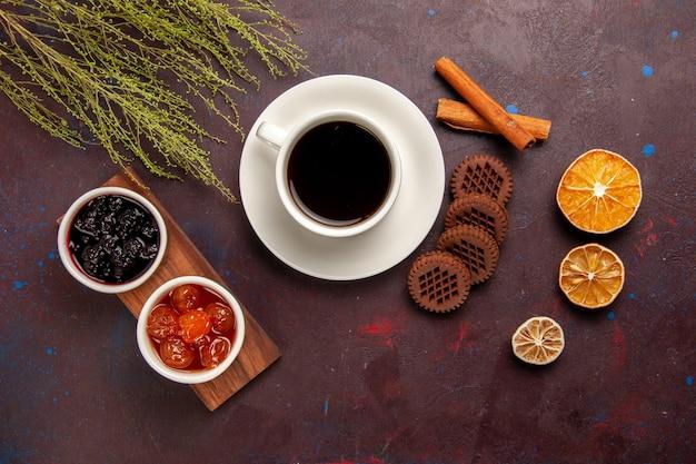 Bovenaanzicht kopje koffie met verschillende soorten jam en chocoladekoekjes op het donkere bureau fruit jam marmelade zoet