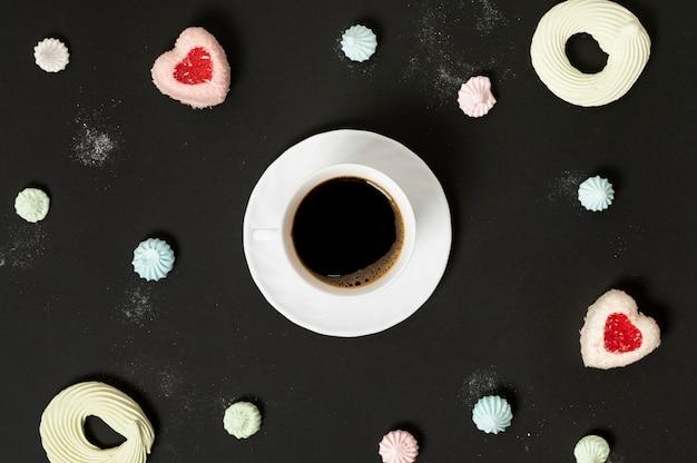 Bovenaanzicht kopje koffie omgeven door meringue cookies