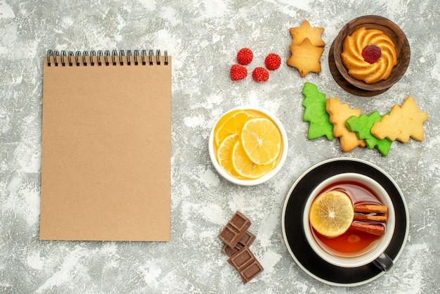 Bovenaanzicht kopje thee citroen plakjes in kom notebook op grijs oppervlak