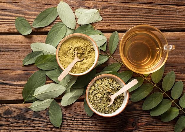 Bovenaanzicht kopje thee en natuurlijke kruiden bladeren
