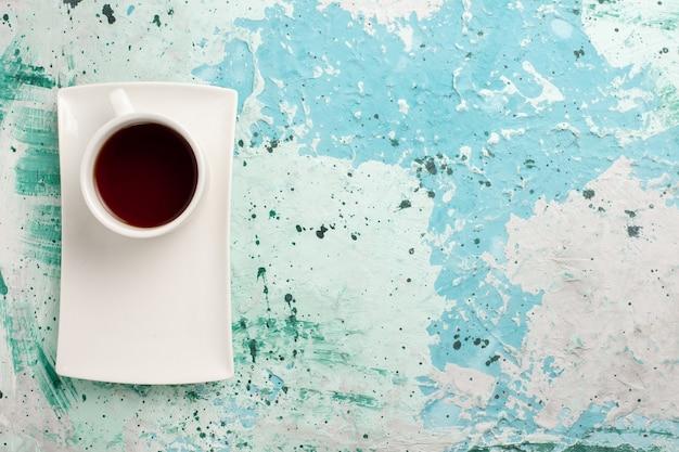 Bovenaanzicht kopje thee in beker en plaat op lichtblauwe ondergrond
