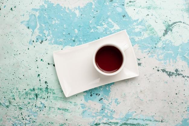 Bovenaanzicht kopje thee in kopje en bord op het lichtblauwe bureau