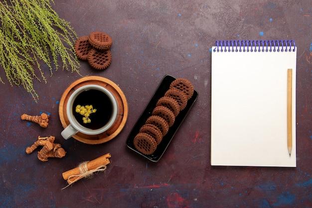 Bovenaanzicht kopje thee in plaat en kopje op donkere achtergrond thee drinken kleurenfoto zoet