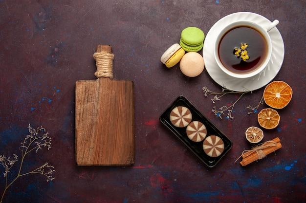 Bovenaanzicht kopje thee in plaat en kopje op donkere achtergrond thee drinken kleurenfoto zoet Gratis Foto