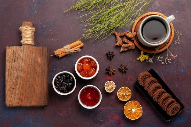 Bovenaanzicht kopje thee in plaat en kopje op donkere ondergrond thee drinken kleurenfoto zoet
