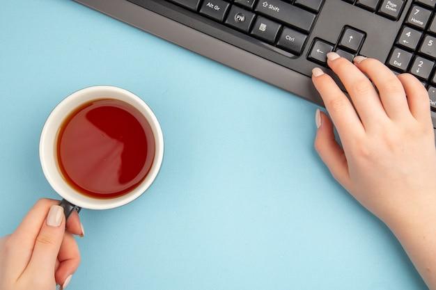 Bovenaanzicht kopje thee in vrouwelijke hand toetsenbord op blauwe tafel