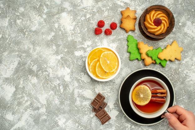 Bovenaanzicht kopje thee koekje in kom kerstboom cookies op grijze oppervlakte vrije ruimte