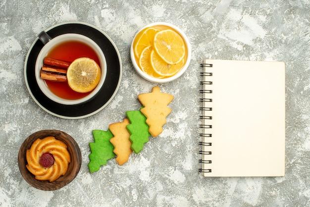 Bovenaanzicht kopje thee koekjes kom met citroen plakjes notebook op grijs oppervlak