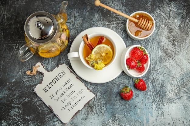 Bovenaanzicht kopje thee met aardbeien en honing op donkere ondergrond fruit theebes