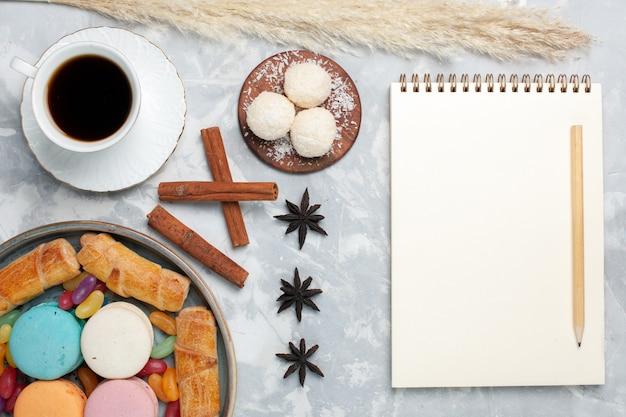 Bovenaanzicht kopje thee met bagels en macarons o wit bureau