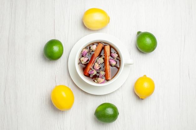 Bovenaanzicht kopje thee met bloemen en citroenen op licht wit bureau