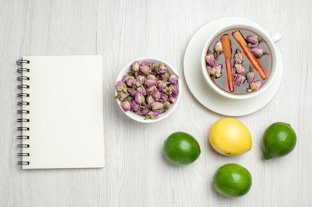 Bovenaanzicht kopje thee met bloemen en citroenen op wit bureau
