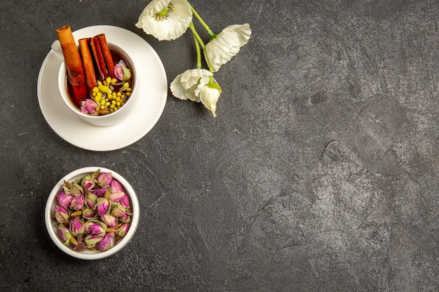 Bovenaanzicht kopje thee met bloemen en kaneel op een grijze achtergrond theekleur regenboogsmaak