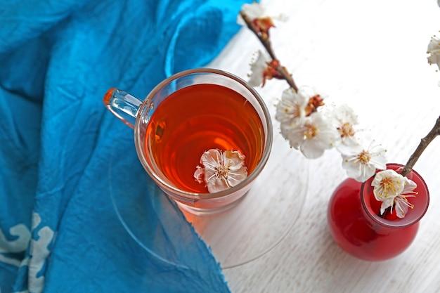 Bovenaanzicht kopje thee met bloemen in een vaas