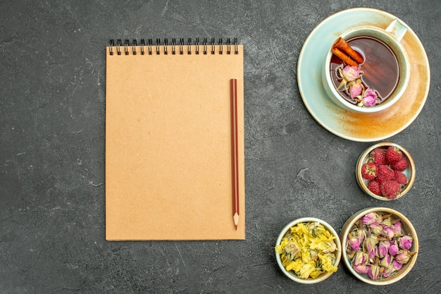 Bovenaanzicht kopje thee met bloemen op de grijze bureautheeceremoniebloem