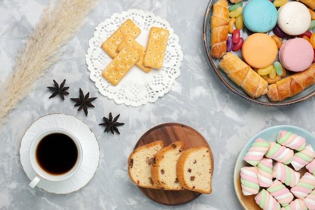 Bovenaanzicht kopje thee met cake bagels en macarons op wit