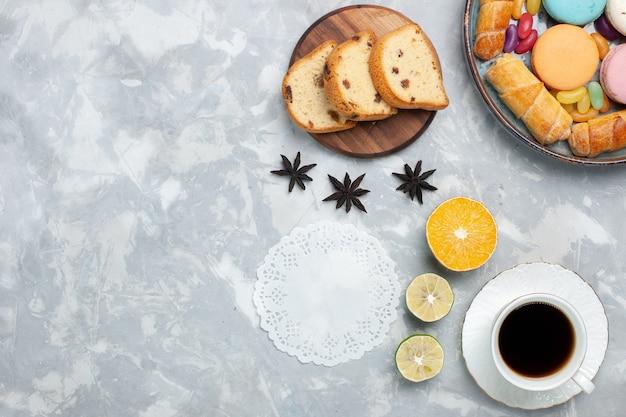 Bovenaanzicht kopje thee met cake en bagels op licht wit