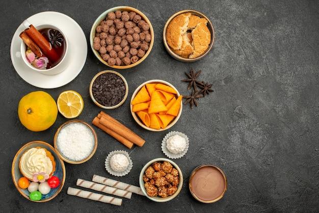 Bovenaanzicht kopje thee met chips en cake op donkere ondergrond cookie candy biscuit cake pie sweet