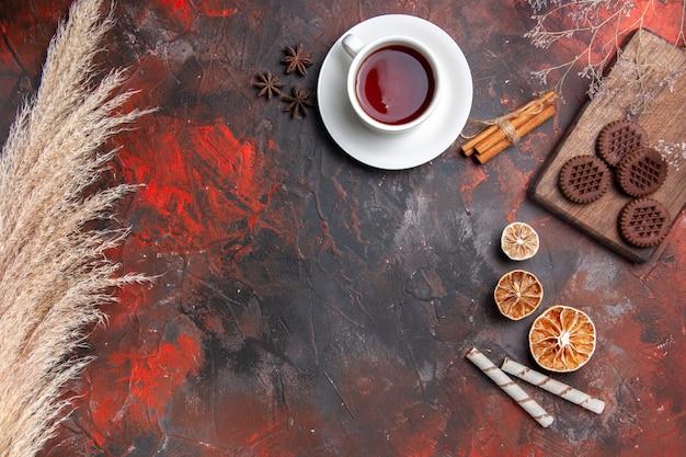 Bovenaanzicht kopje thee met choco cookies op donkere tafel donkere koekje