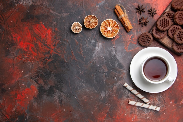 Bovenaanzicht kopje thee met choco cookies op donkere tafel koekjes theekoekje