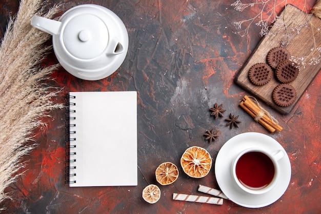 Bovenaanzicht kopje thee met choco cookies op donkere tafel thee koekje