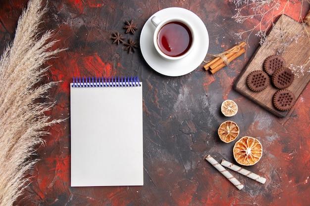 Bovenaanzicht kopje thee met choco cookies op het donkere koekje van de tafelfoto