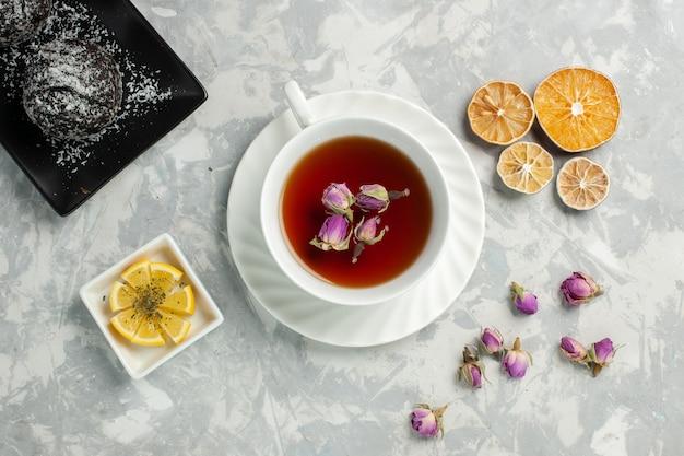 Bovenaanzicht kopje thee met chocoladetaart op licht wit bureau