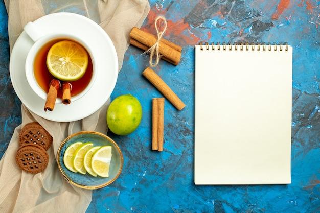Bovenaanzicht kopje thee met citroen en kaneel beige sjaal koekjes citroen notebook op blauw rood oppervlak