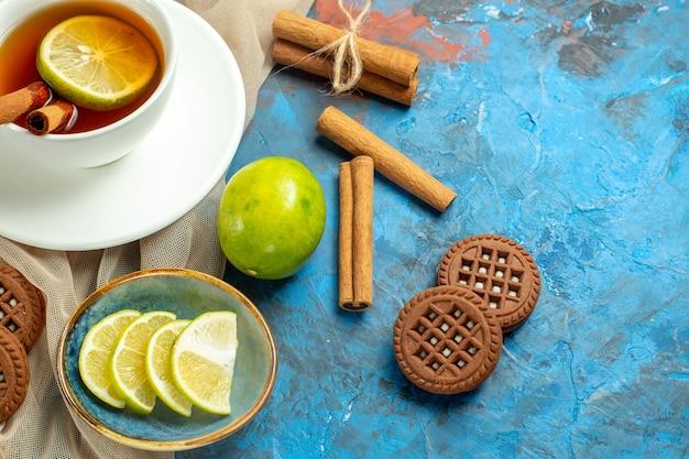 Bovenaanzicht kopje thee met citroen en kaneel beige sjaalkoekjes citroen op blauw rood tafel kopie plaats